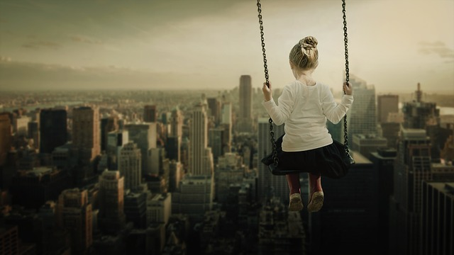 A girl on a swing overlooking a city